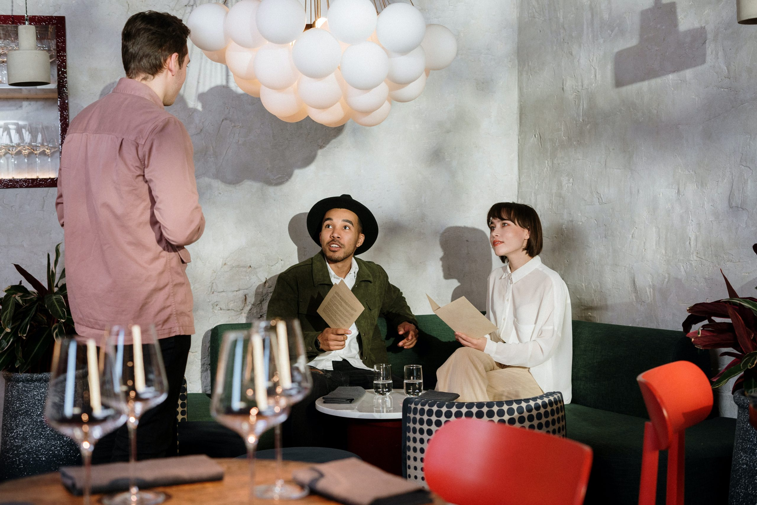 New restaurant concepts like the one photographed where a waiter is speaking to a couple with menus in their hands, is one facet of the latest restaurant industry news and trends.