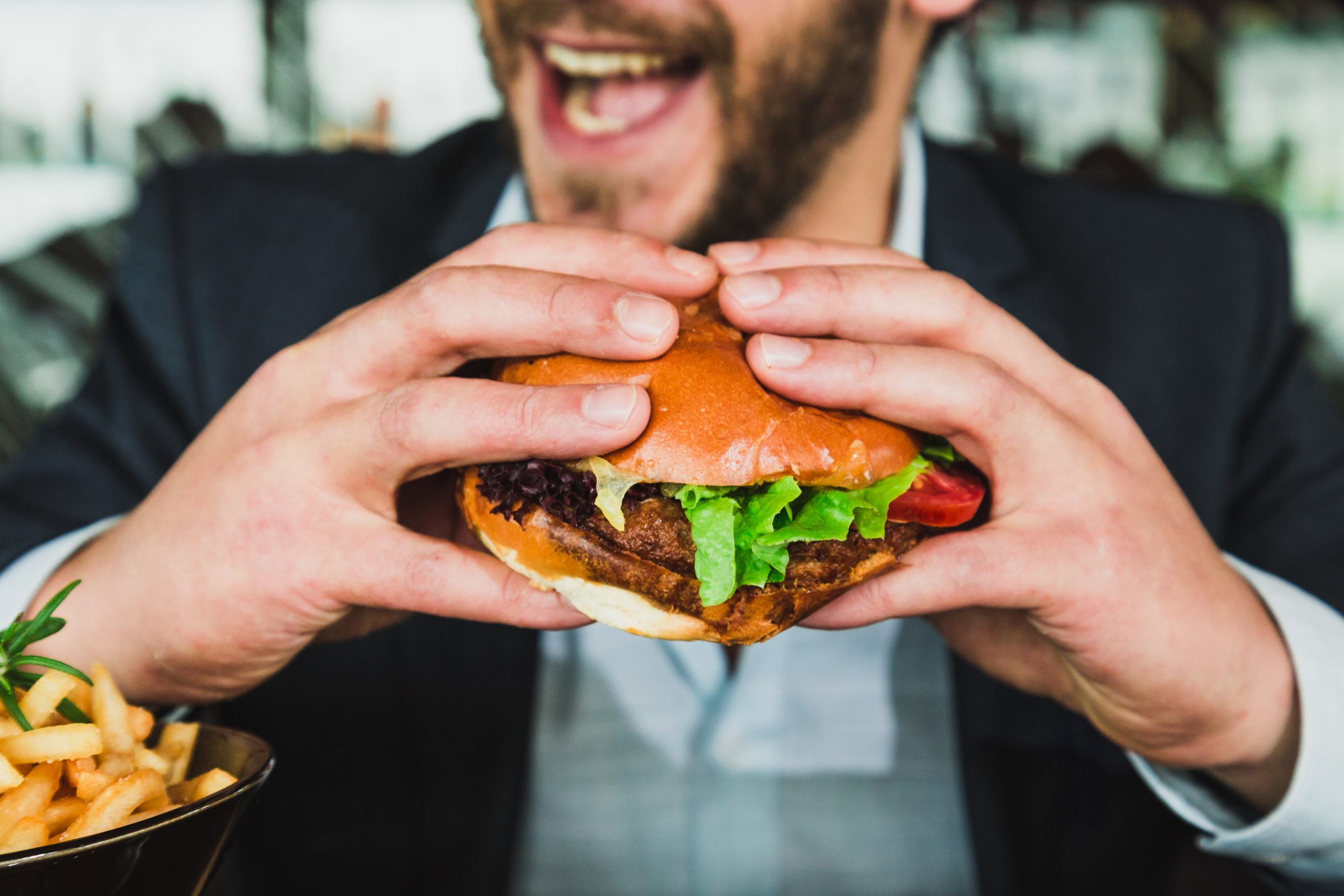 A man in a suit holding a burger and smiling after ordering from Sixdots instead of Bite Squad for restaurants.
