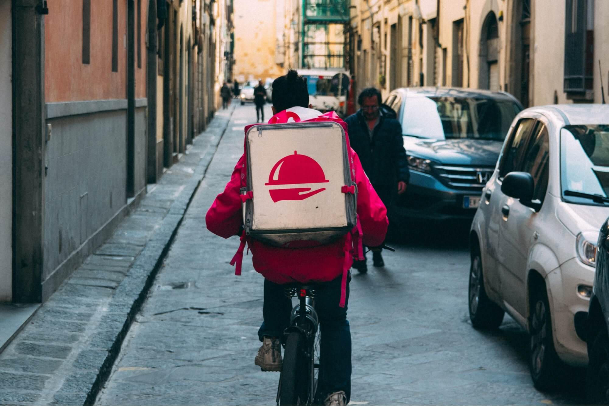 A man in a red jacket on a bicycle with a delivery box on his back making his rounds for Delivery Dudes for restaurants.