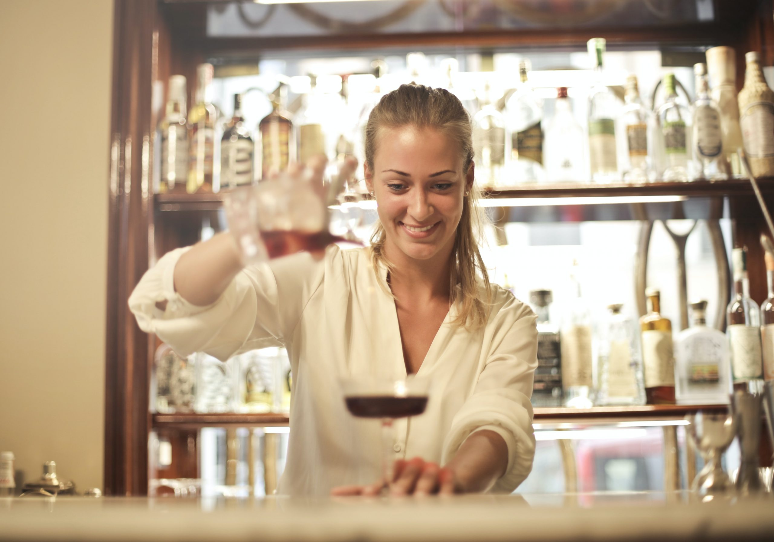 Female hospitality leaders like the one shown pouring a cocktail are paving the way for others in the hospitality industry.