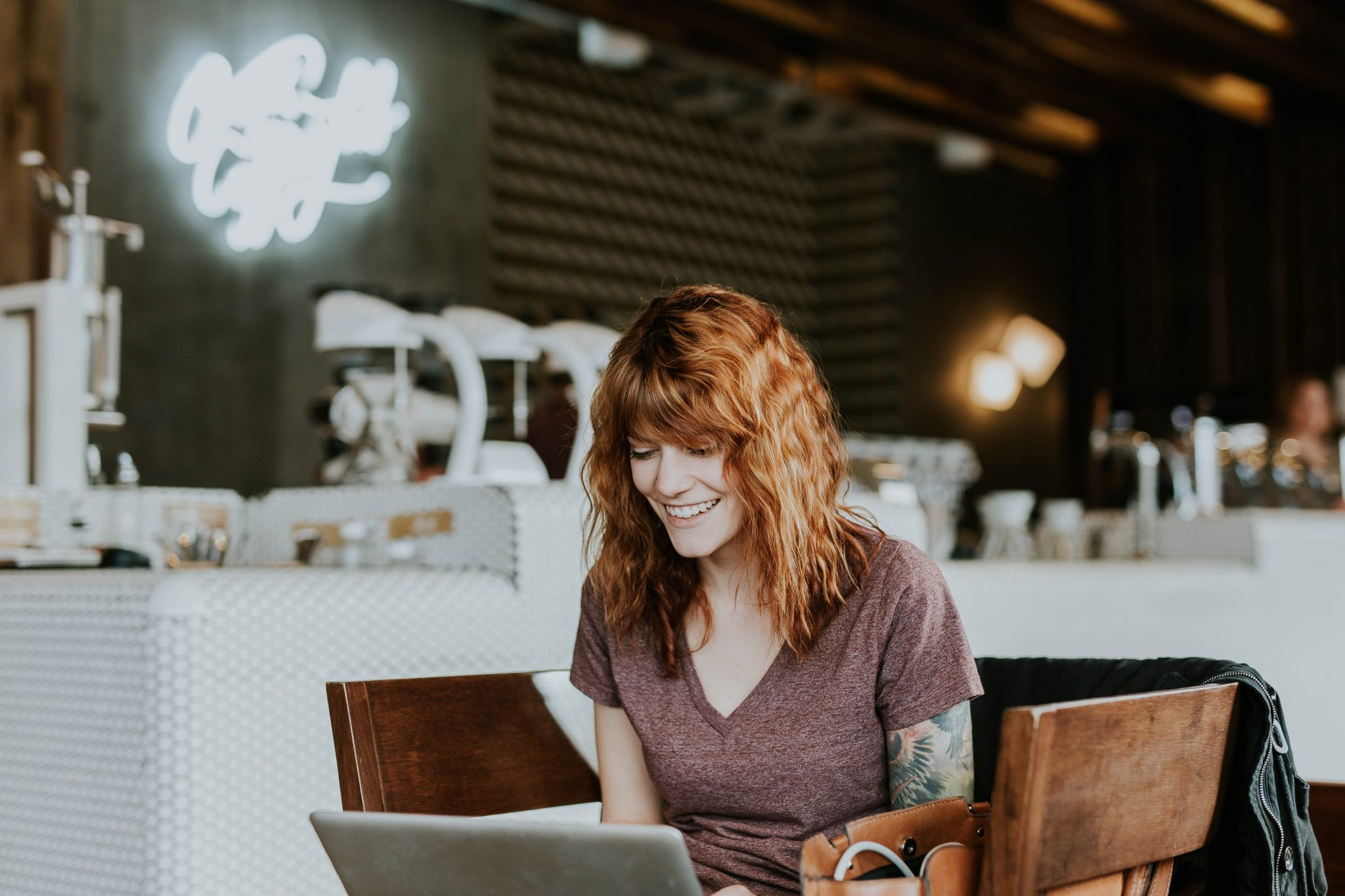 A customer with red hair sitting at a table in a restuaurant with her laptop answering restaurant survey questions after her meal.