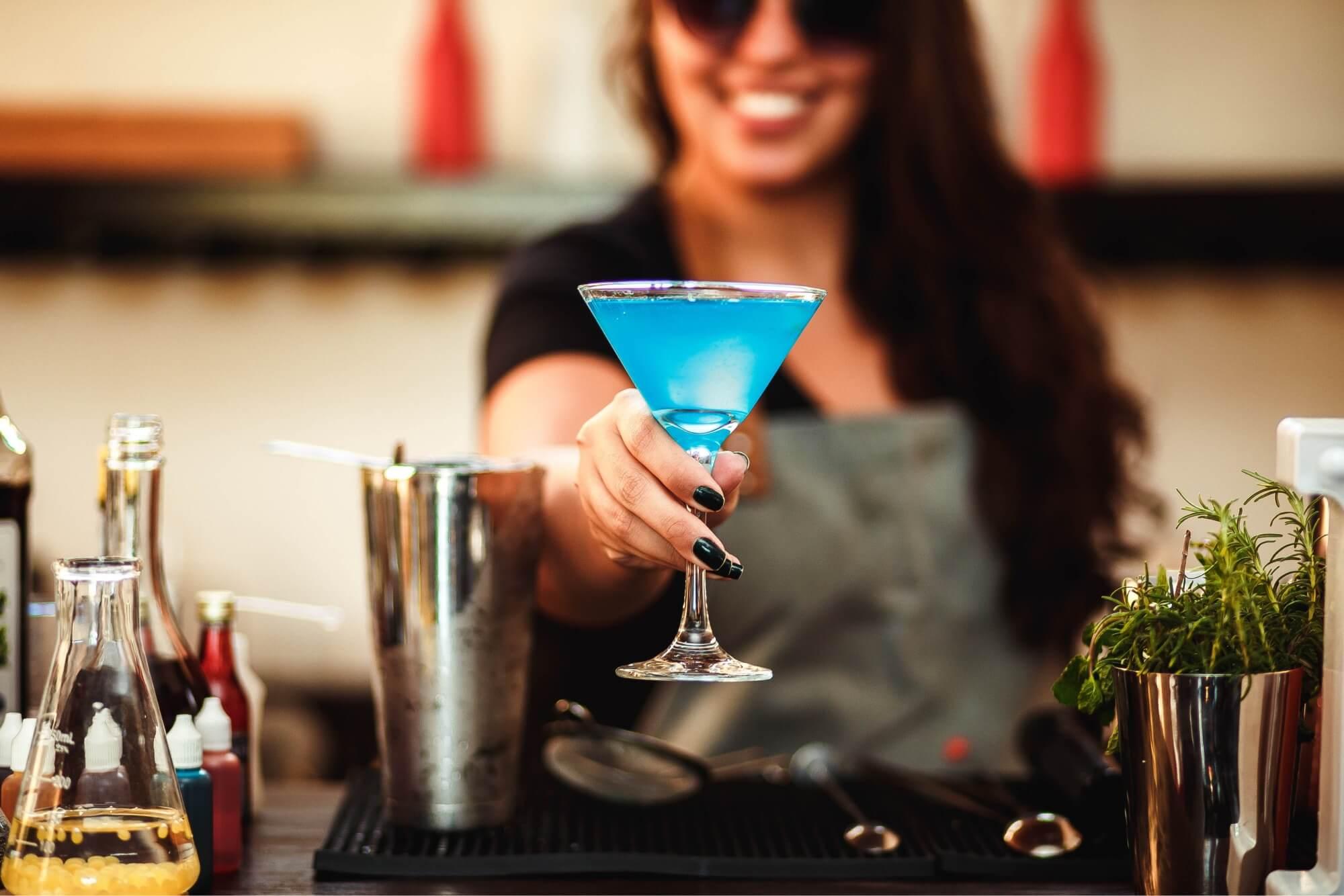 A bartender serving a blue martini at a bar that has a liquor license.