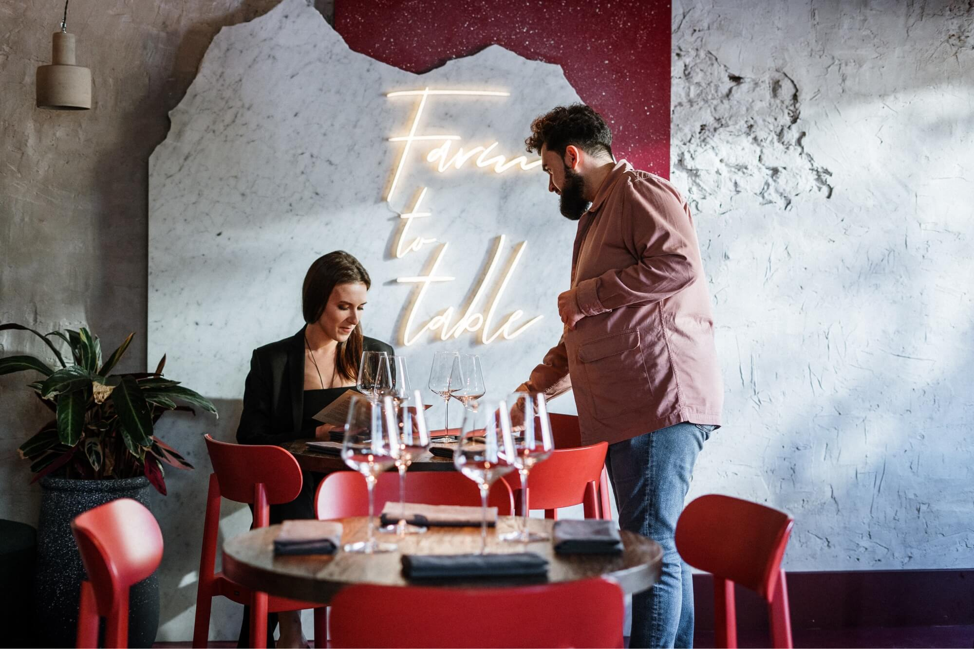 After following good restaurant design tips, this restaurant owner is speaking with a customer at his farm-to-table themed restaurant that makes use of the color red in the chairs and wall backsplash.