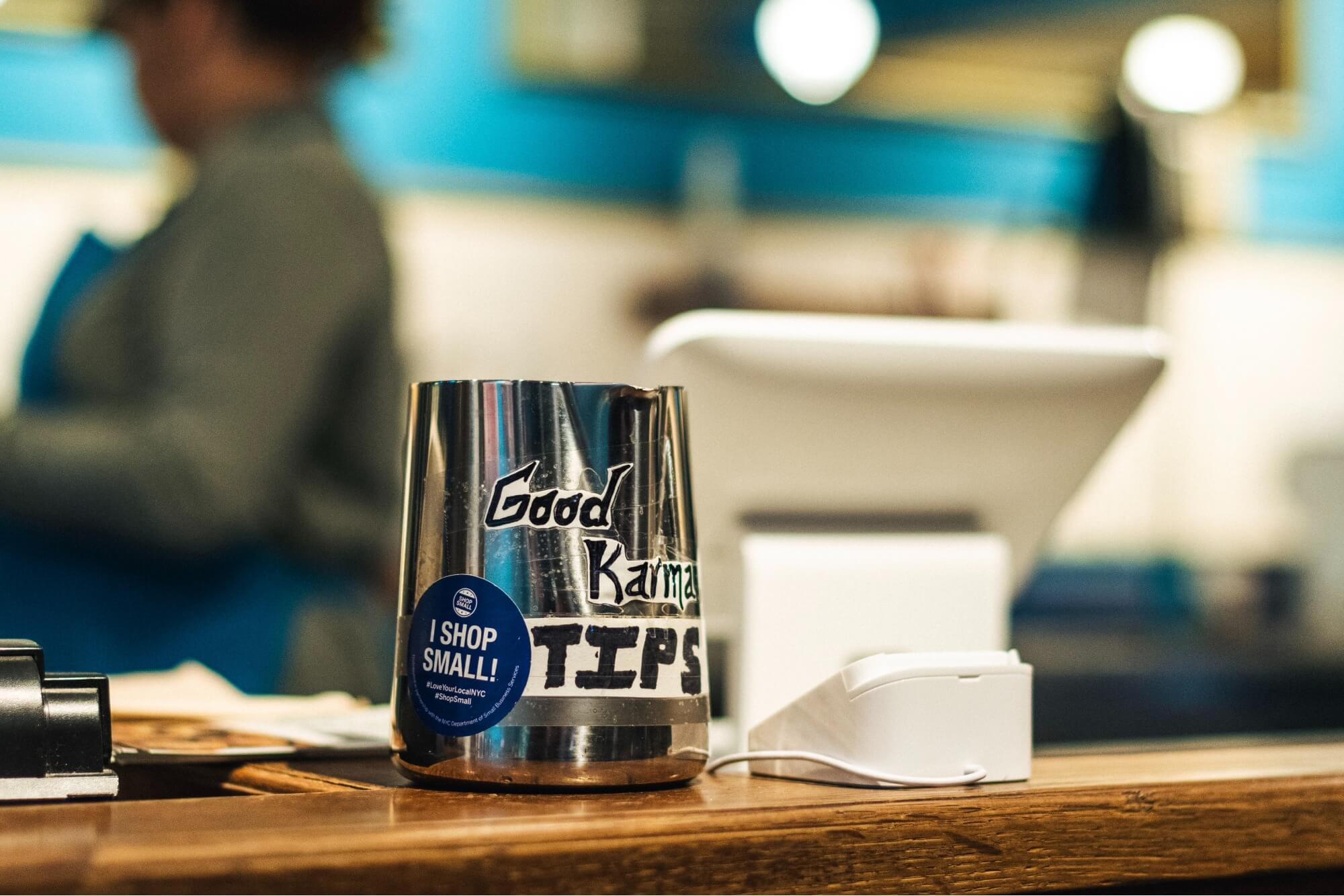 """A metal tip jar that reads """"Good Karma Tips"""" placed on a wooden counter next to a POS system at a restaurant that practices tip pooling."""