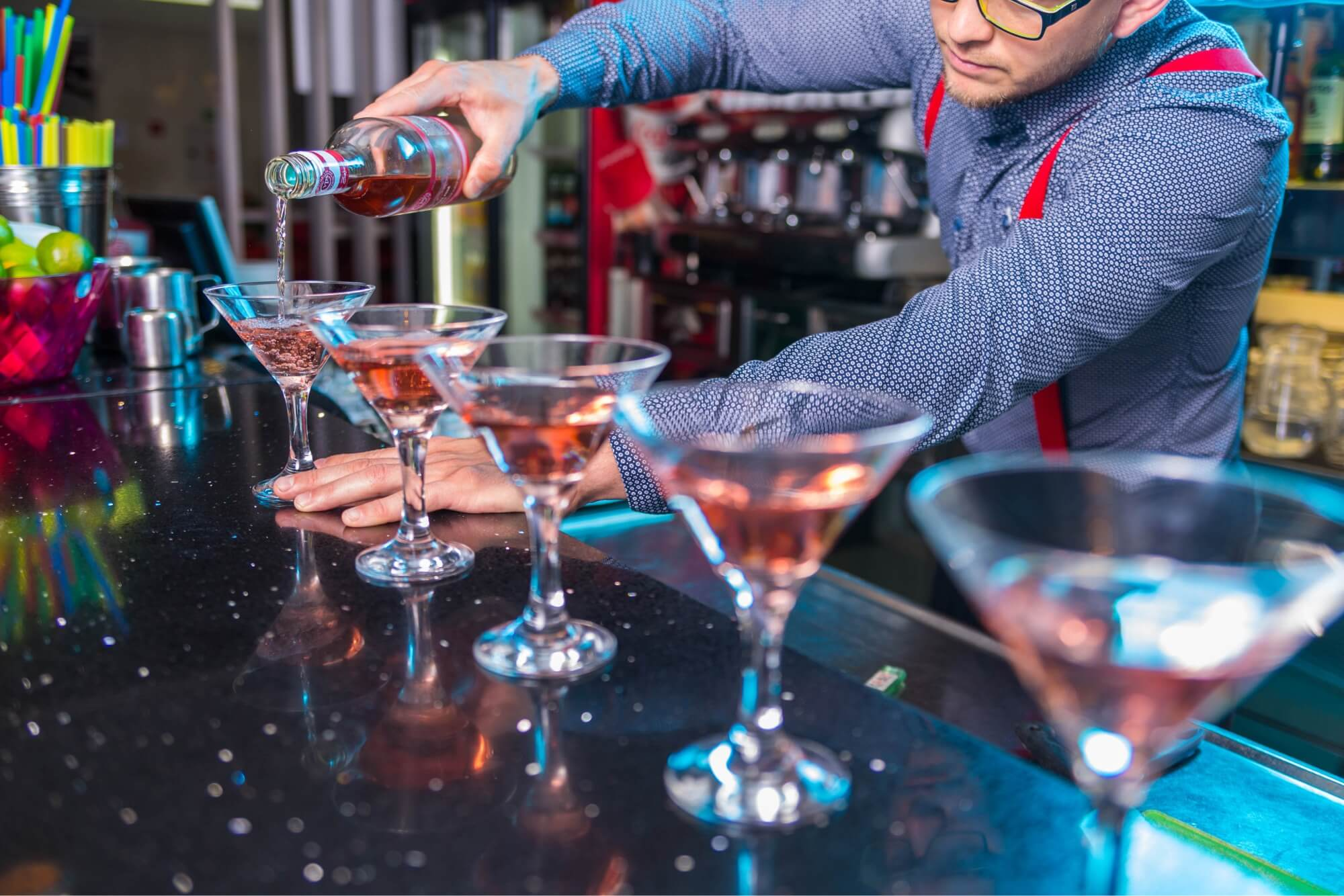 After opening a bar, this bartender, wearing a long sleeve blue button down with red suspenders, is serving 5 cosmopolitan martinis.