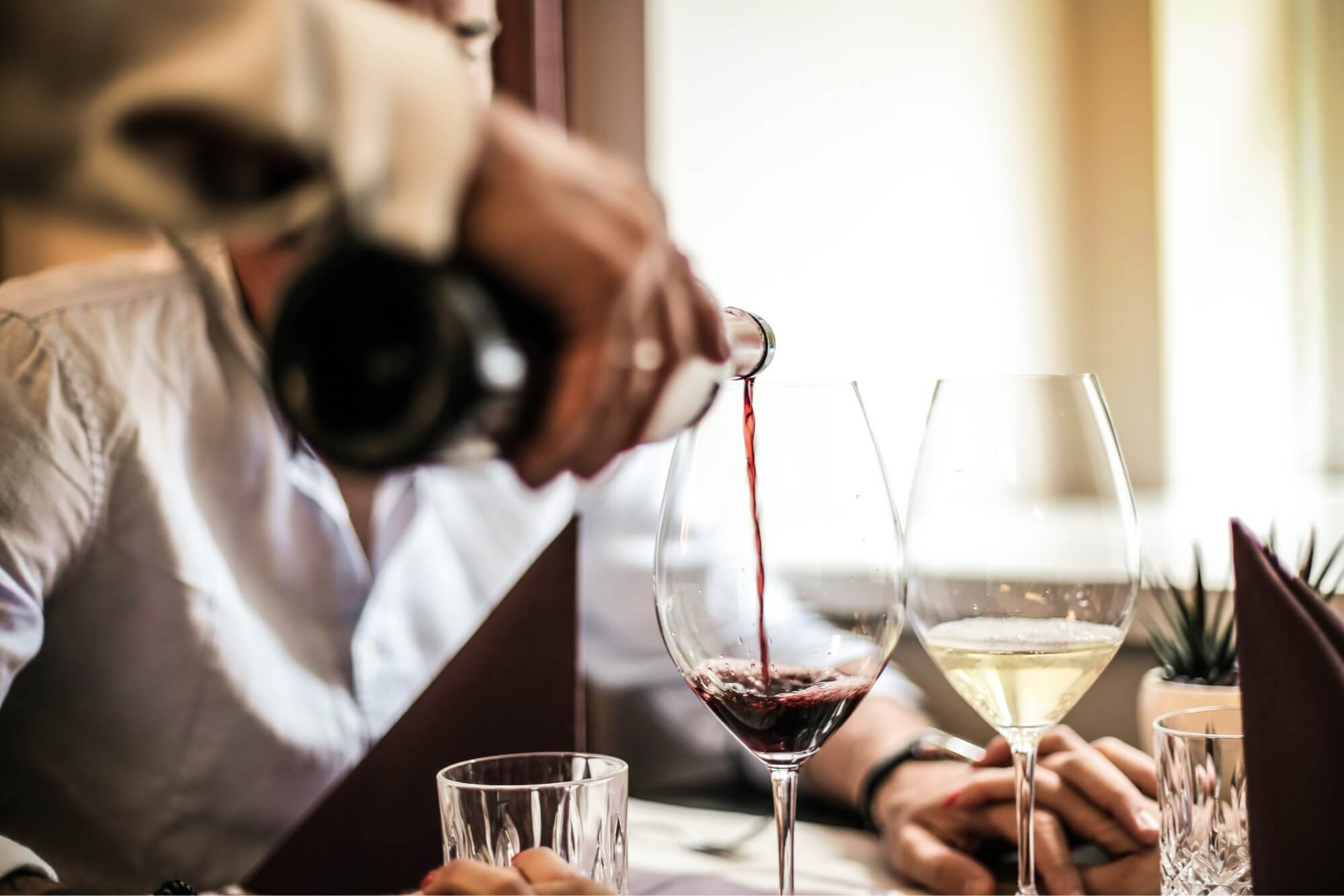 A hand pouring a glass of red wine at a fine dining restaurant that charges corkage fees.